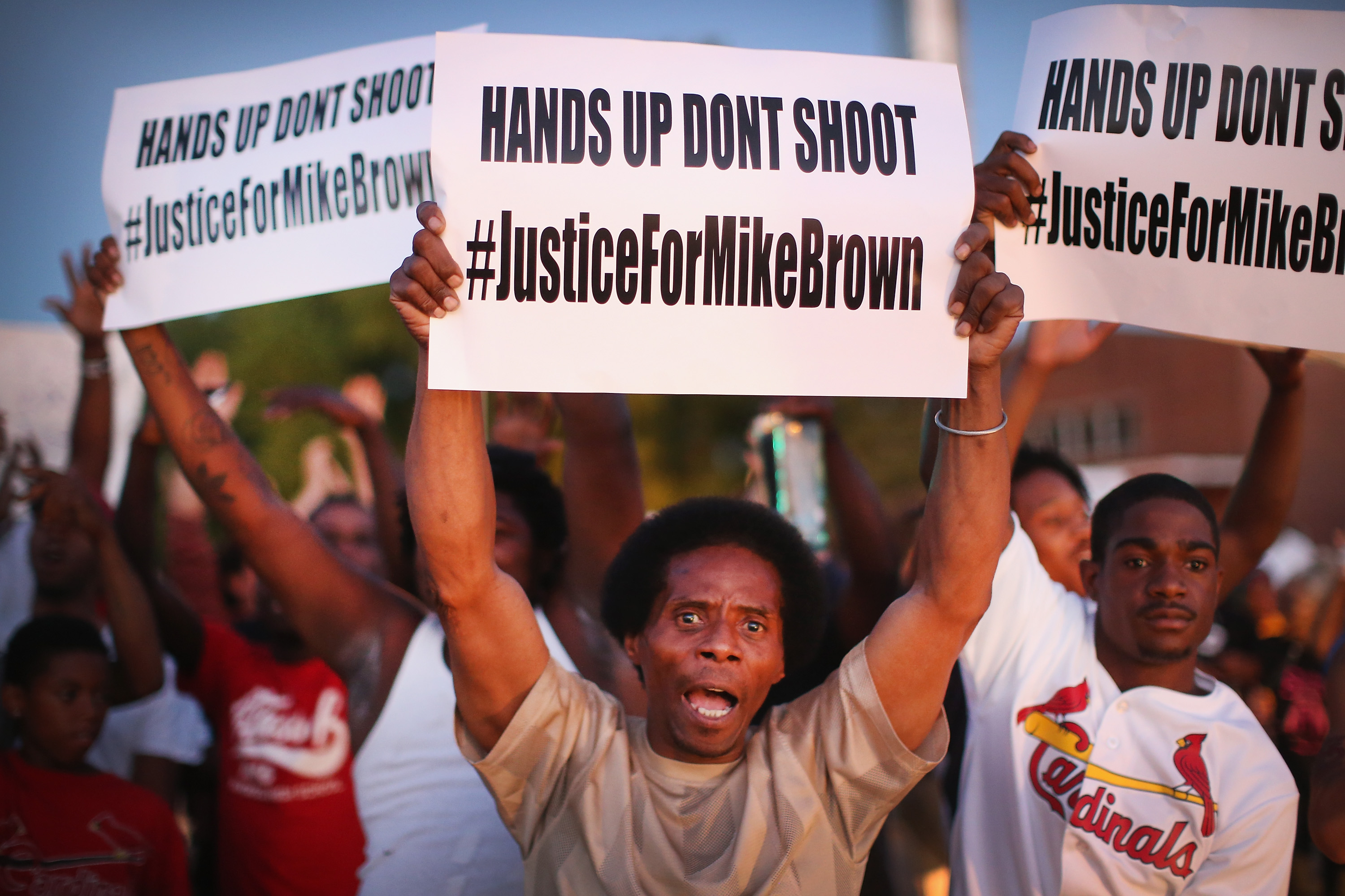 ST. LOUIS, MO - AUGUST 12: Demonstrators protest the killing of teenager Michael Brown outside Greater St. Marks Family Church while Browns family along with civil rights leader Rev. Al Sharpton and a capacity crowd of guests met inside to discuss the killing on August 12, 2014 in St Louis, Missouri. Brown was shot and killed by a police officer on Saturday in the nearby suburb of Ferguson. Ferguson has experienced two days of violent protests since the killing but, tonight the town remained mostly peaceful.  (Photo by Scott Olson/Getty Images)