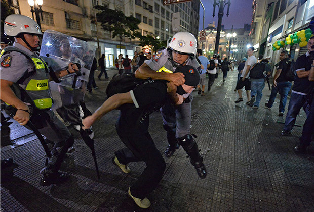 Policemen hit a demonstrator during a protest against the government's expenditure for the 2014 FIFA World Cup in Sao Paulo, Brazil on February 22, 2014.