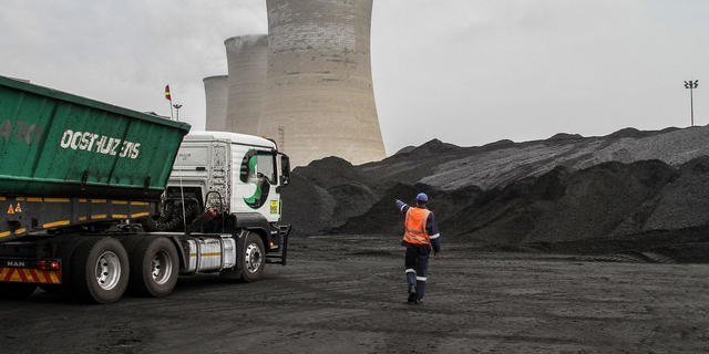 A worker supervises as a truck delivers coal supplies to the coal yard at the Grootvlei power station, operated by Eskom Holdings SOC Ltd., in Grootvlei, South Africa, on Monday, Nov. 3, 2014. Eskom said South Africa's power supply remains strained as it investigates what caused a silo storing coal to collapse, forcing the state-owned utility to cut electricity to customers. Photographer: Dean Hutton/Bloomberg