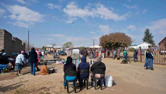 "The ANC has privatised services like pension delivery: ""People's engagement on the first of each month is rarely with the state, but with bank tellers, CPS agents, ATMs and grocery store clerks, places where the state is, in effect, absent"". Here, three women who work for a loan shark wait for grant recipients in Thembalihle township in the Free State."