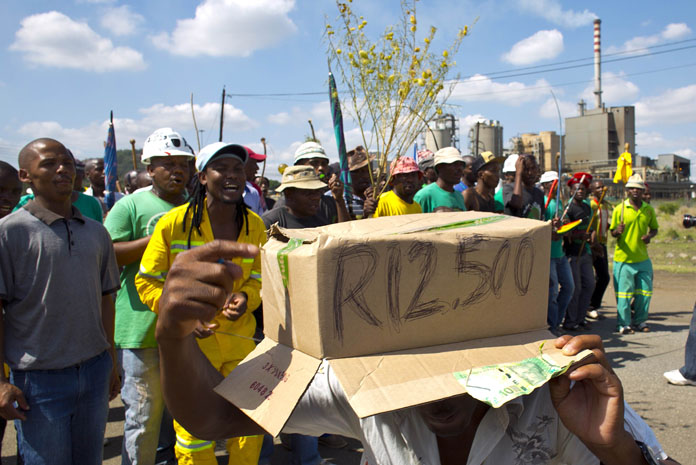 "A striking miner holds a cardboard box on his head with text reading ""12,500 Rands"" as striking miners chant slogans while marching to Wonderkop Stadium near Lonmin's platinum mine in Marikana on January 23, 2014. AFP PHOTO / ALEXANDER JOE"