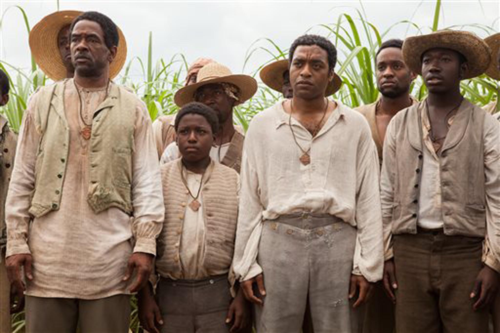 "This image released by Fox Searchlight shows Chiwetel Ejiofor, second right, in a scene from ""12 Years A Slave.""  (AP Photo/Fox Searchlight, Francois Duhamel)"